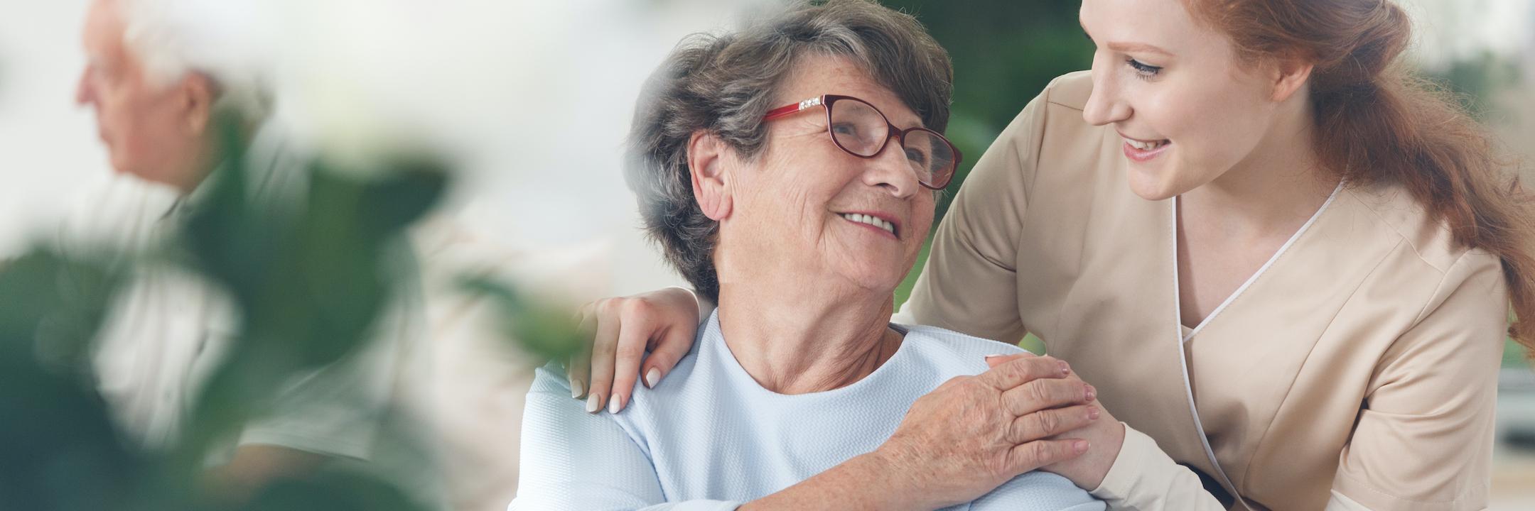 Professional helpful caregiver comforting smiling senior woman at nursing home